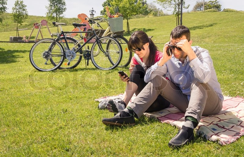 10503302-couple-in-love-using-a-smartphones-on-the-park